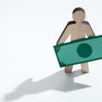 Wooden man with dollars standing on white background